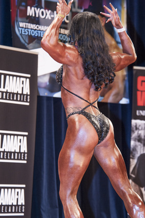 national championship: SCHIEDAM, THE NETHERLANDS - APRIL 26, 2015: Female bikini model, power amazon and muscle lady shows her best back double biceps pose at the 38th Dutch National Championship Bodybuilding and Fitness of the IFBB Netherlands (NBBF) on april 26, 2015 in Theat Editorial