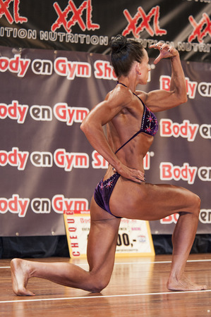 national championship: SCHIEDAM, THE NETHERLANDS - APRIL 26, 2015: Female bikini fitness and physique model Mariska Meuwissen shows her big biceps on stage at the 38th Dutch National Championship Bodybuilding and Fitness of the IFBB Netherlands (NBBF) on april 26, 2015 in Theat