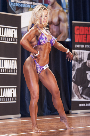 schiedam: SCHIEDAM, THE NETHERLANDS - APRIL 26, 2015: Female bikini fitness model Evelien Nellen shows her best at the 38th Dutch National Championship Bodybuilding and Fitness of the IFBB Netherlands (NBBF) on april 26, 2015 in Theatre aan de Schie at Schiedam,  Editorial