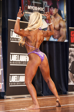 national championship: SCHIEDAM, THE NETHERLANDS - APRIL 26, 2015: Female bikini fitness model Evelien Nellen shows her best back double biceps pose at the 38th Dutch National Championship Bodybuilding and Fitness of the IFBB Netherlands (NBBF) on april 26, 2015 in Theatre aan