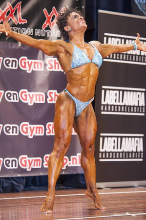 schiedam: SCHIEDAM, THE NETHERLANDS - APRIL 26, 2015: Female bikini fitness model Floor van Putten shows her happiness on stage at the 38th Dutch National Championship Bodybuilding and Fitness of the IFBB Netherlands (NBBF) on april 26, 2015 in Theatre aan de Schi