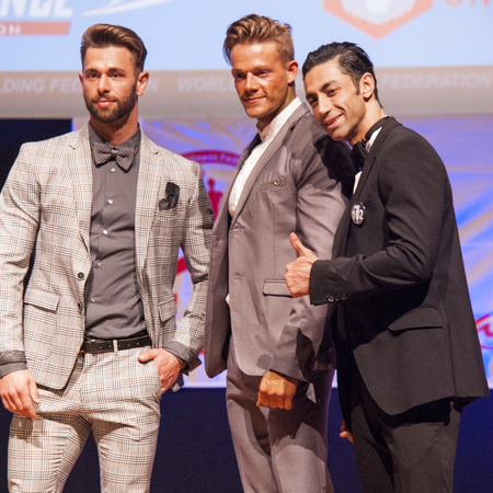 flex: MAASTRICHT, THE NETHERLANDS - OCTOBER 25, 2015: Male fitness models Ali Dalili from Iran, Maxime Maurissen and Joy Flex dressed in suit show their best on stage at the World Grandprix Bodybuilding and Fitness of the WBBF-WFF on October 25, 2015 at the MEC
