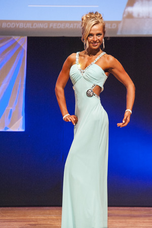 thea: MAASTRICHT, THE NETHERLANDS - OCTOBER 25, 2015: Female fitness model Larissa van Meerten in evening dress shows her best physique in championship on stage at the World Grandprix Bodybuilding and Fitness of the WBBF-WFF on October 25, 2015 at the MECC Thea