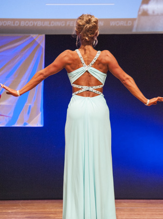 MAASTRICHT, THE NETHERLANDS - OCTOBER 25, 2015: Female fitness model Larissa van Meerten in evening dress shows her best physique in championship on stage at the World Grandprix Bodybuilding and Fitness of the WBBF-WFF on October 25, 2015 at the MECC Thea