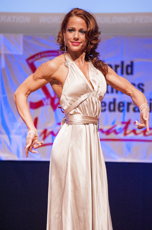 physique: MAASTRICHT, THE NETHERLANDS - OCTOBER 25, 2015: Female fitness model Eline Demeulemeester in evening dress shows her best physique in championship on stage at the World Grandprix Bodybuilding and Fitness of the WBBF-WFF on October 25, 2015 at the MECC The Editorial