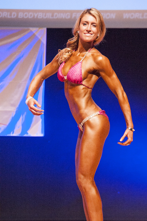 physique: MAASTRICHT, THE NETHERLANDS - OCTOBER 25, 2015: Female physique model Femke van Neck shows her best sidepose at championship on stageat the World Grandprix Bodybuilding and Fitness of the WBBF-WFF on October 25, 2015 at the MECC Theatre in Maastricht, the Editorial