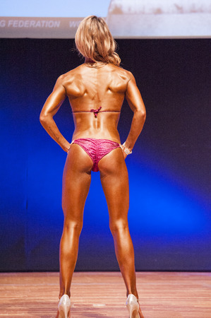 physique: MAASTRICHT, THE NETHERLANDS - OCTOBER 25, 2015: Female physique model Femke van Neck shows her best back pose at championship on stageat the World Grandprix Bodybuilding and Fitness of the WBBF-WFF on October 25, 2015 at the MECC Theatre in Maastricht, th