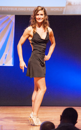 physique: MAASTRICHT, THE NETHERLANDS - OCTOBER 25, 2015: Female fitness model Katja Boons in evening dress shows her best physique in championship on stage at the World Grandprix Bodybuilding and Fitness of the WBBF-WFF on October 25, 2015 at the MECC Theatre in M Editorial