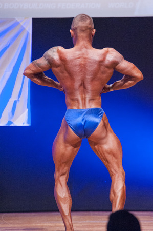 lats: MAASTRICHT, THE NETHERLANDS - OCTOBER 25, 2015: Male bodybuilder Dennis Theys flexes his muscles and shows his best lats spread pose at the World Grandprix Bodybuilding and Fitness of the WBBF-WFF on October 25, 2015 at the MECC Theatre in Maastricht, the Editorial