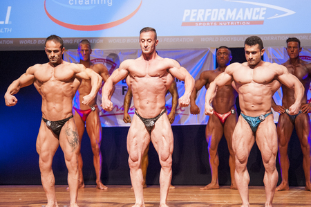 nether: MAASTRICHT, THE NETHERLANDS - OCTOBER 25, 2015: Male bodybuilders flex their muscles and shows their best front pose on stage at the World Grandprix Bodybuilding and Fitness of the WBBF-WFF on October 25, 2015 at the MECC Theatre in Maastricht, the Nether