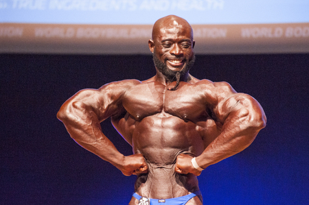 lats: MAASTRICHT, THE NETHERLANDS - OCTOBER 25, 2015: Male bodybuilder Elias Bogane flexes his muscles and shows his best physique in a front lats spread pose on stage at the World Grandprix Bodybuilding and Fitness of the WBBF-WFF on October 25, 2015 at the ME Editorial