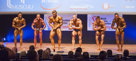 physique: MAASTRICHT, THE NETHERLANDS - OCTOBER 25, 2015: Male bodybuilders Ali Rezah from Iran with other competitors flex their muscles and show their best physique in a most muscular pose on stage at the World Grandprix Bodybuilding and Fitness of the WBBF-WFF o Editorial