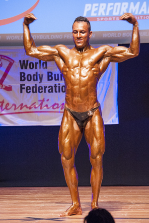 physique: MAASTRICHT, THE NETHERLANDS - OCTOBER 25, 2015: Male bodybuilder Ali Rezah from Iran flexes his muscles and shows his best physique in a front double biceps pose on stage at the World Grandprix Bodybuilding and Fitness of the WBBF-WFF on October 25, 2015