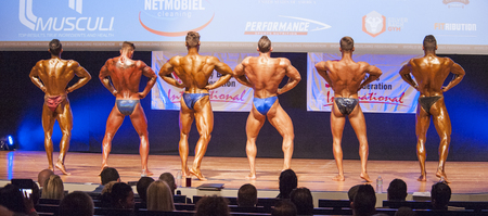 lats: MAASTRICHT, THE NETHERLANDS - OCTOBER 25, 2015: Male bodybuilders Ali Rezah from Iran with other competitors flex their muscles and show their best physique in a lats spread pose on stage at the World Grandprix Bodybuilding and Fitness of the WBBF-WFF on  Editorial