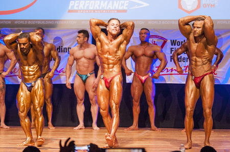 flex: MAASTRICHT, THE NETHERLANDS - OCTOBER 25, 2015: Male bodybuilders flex their muscles and shows their best abdominal and thighs pose on stage at the World Grandprix Bodybuilding and Fitness of the WBBF-WFF on October 25, 2015 at the MECC Theatre in Maastri