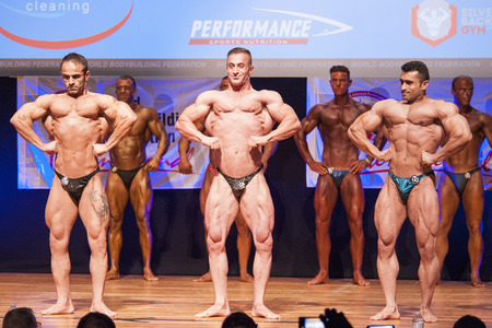 lats: MAASTRICHT, THE NETHERLANDS - OCTOBER 25, 2015: Male bodybuilders flex their muscles and shows their best lats spread front pose on stage at the World Grandprix Bodybuilding and Fitness of the WBBF-WFF on October 25, 2015 at the MECC Theatre in Maastricht Editorial