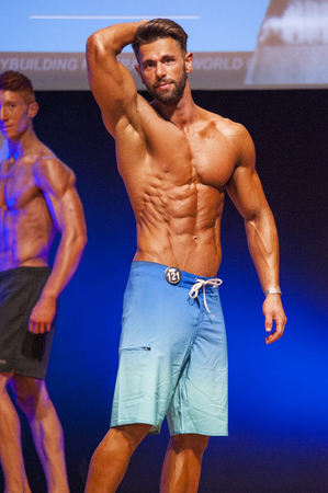 physique: MAASTRICHT, THE NETHERLANDS - OCTOBER 25, 2015: Male physique model Maxime Maurissen shows his best front pose at championship on stage at the World Grandprix Bodybuilding and Fitness of the WBBF-WFF on October 25, 2015 at the MECC Theatre in Maastricht,
