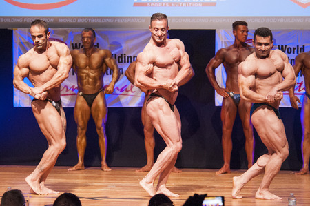 nether: MAASTRICHT, THE NETHERLANDS - OCTOBER 25, 2015: Male bodybuilders flex their muscles and shows their best chest pose on stage at the World Grandprix Bodybuilding and Fitness of the WBBF-WFF on October 25, 2015 at the MECC Theatre in Maastricht, the Nether Editorial