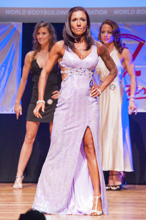 physique: MAASTRICHT, THE NETHERLANDS - OCTOBER 25, 2015: Female fitness model Deborah van Kolck in evening dress shows her best physique in championship on stage at the World Grandprix Bodybuilding and Fitness of the WBBF-WFF on October 25, 2015 at the MECC Theatr