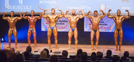 physique: MAASTRICHT, THE NETHERLANDS - OCTOBER 25, 2015: Male bodybuilders Ali Rezah from Iran with other competitors flex their muscles and show their best physique in a front double biceps pose on stage at the World Grandprix Bodybuilding and Fitness of the WBBF Editorial