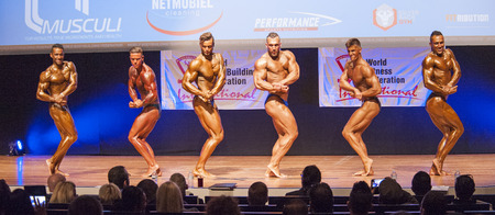 physique: MAASTRICHT, THE NETHERLANDS - OCTOBER 25, 2015: Male bodybuilders Ali Rezah from Iran with other competitors flex their muscles and show their best physique in a chest pose on stage at the World Grandprix Bodybuilding and Fitness of the WBBF-WFF on Octobe