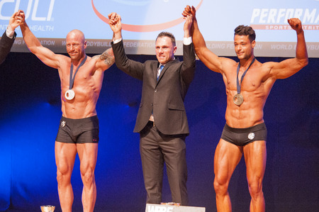 nether: MAASTRICHT, THE NETHERLANDS - OCTOBER 25, 2015: Male bodybuilders Erik Stobbe celebrate their victory with officials on stage at the World Grandprix Bodybuilding and Fitness of the WBBF-WFF on October 25, 2015 at the MECC Theatre in Maastricht, the Nether