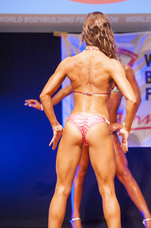 maas: MAASTRICHT, THE NETHERLANDS - OCTOBER 25, 2015: Female fitness bikini model Kimberly Goethals shows her best back pose at championship on stage at the World Grandprix Bodybuilding and Fitness of the WBBF-WFF on October 25, 2015 at the MECC Theatre in Maas