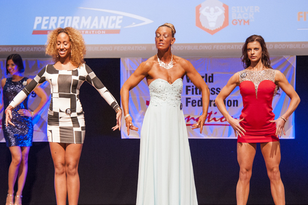 physique: MAASTRICHT, THE NETHERLANDS - OCTOBER 25, 2015: Female fitness models in evening dress show their best physique in championship on stage at the World Grandprix Bodybuilding and Fitness of the WBBF-WFF on October 25, 2015 at the MECC Theatre in Maastricht,