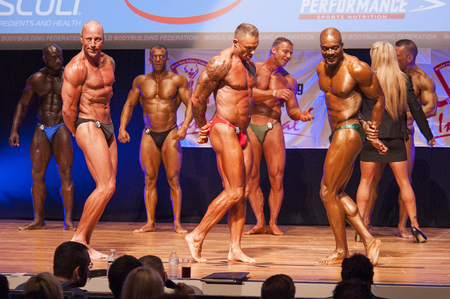 physique: MAASTRICHT, THE NETHERLANDS - OCTOBER 25, 2015: Male bodybuilders flex their muscles and show their best physique in a triceps pose on stage at the World Grandprix Bodybuilding and Fitness of the WBBF-WFF on October 25, 2015 at the MECC Theatre in Maastri