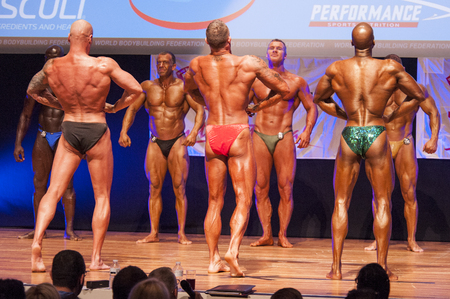 maas: MAASTRICHT, THE NETHERLANDS - OCTOBER 25, 2015: Male bodybuilders flex their muscles and show their best physique in a lats spreadpose on stage at the World Grandprix Bodybuilding and Fitness of the WBBF-WFF on October 25, 2015 at the MECC Theatre in Maas