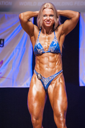 physique: MAASTRICHT, THE NETHERLANDS - OCTOBER 25, 2015: Female fitness model Kinga Golebiewska flexes her muscles and shows her best physique in a abdominal and thighs pose on stage at the World Grandprix Bodybuilding and Fitness of the WBBF-WFF on October 25, 20