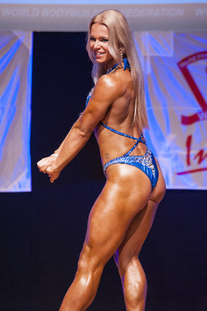physique: MAASTRICHT, THE NETHERLANDS - OCTOBER 25, 2015: Female fitness model Kinga Golebiewska flexes her muscles and shows her best physique in a back pose on stage at the World Grandprix Bodybuilding and Fitness of the WBBF-WFF on October 25, 2015 at the MECC T