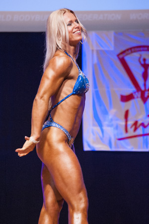 physique: MAASTRICHT, THE NETHERLANDS - OCTOBER 25, 2015: Female fitness model Kinga Golebiewska flexes her muscles and shows her best physique in a sidepose on stage at the World Grandprix Bodybuilding and Fitness of the WBBF-WFF on October 25, 2015 at the MECC Th