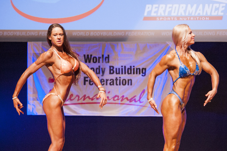 competitor: MAASTRICHT, THE NETHERLANDS - OCTOBER 25, 2015: Female fitness models Kinga Golebiewska and another competitor flex their muscles and show their best physique in a side pose on stage at the World Grandprix Bodybuilding and Fitness of the WBBF-WFF on Octob
