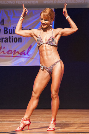 thea: MAASTRICHT, THE NETHERLANDS - OCTOBER 25, 2015: Female fitness model flexes her muscles and shows her best physique in a front double biceps pose on stage at the World Grandprix Bodybuilding and Fitness of the WBBF-WFF on October 25, 2015 at the MECC Thea