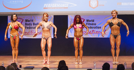 physique: MAASTRICHT, THE NETHERLANDS - OCTOBER 25, 2015: Female fitness models Gerbel Mikk, Sonja den Breems-Tanamal and two other competitors flex their muscles and show their best physique in a front pose on stage at the World Grandprix Bodybuilding and Fitness  Editorial
