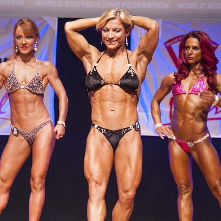 physique: MAASTRICHT, THE NETHERLANDS - OCTOBER 25, 2015: Female fitness model Gerbel Mikk flexes her muscles and shows her best physique in a abdominal and thighs pose on stage at the World Grandprix Bodybuilding and Fitness of the WBBF-WFF on October 25, 2015 at