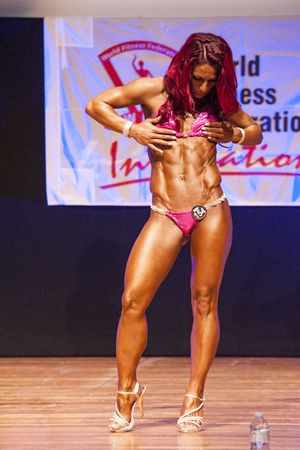 thea: MAASTRICHT, THE NETHERLANDS - OCTOBER 25, 2015: Female fitness model flexes her muscles and shows her best physique in a abdominal and thighspose on stage at the World Grandprix Bodybuilding and Fitness of the WBBF-WFF on October 25, 2015 at the MECC Thea