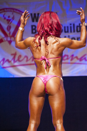 physique: MAASTRICHT, THE NETHERLANDS - OCTOBER 25, 2015: Female fitness model flexes her muscles and shows her best physique in a back pose on stage at the World Grandprix Bodybuilding and Fitness of the WBBF-WFF on October 25, 2015 at the MECC Theatre in Maastric
