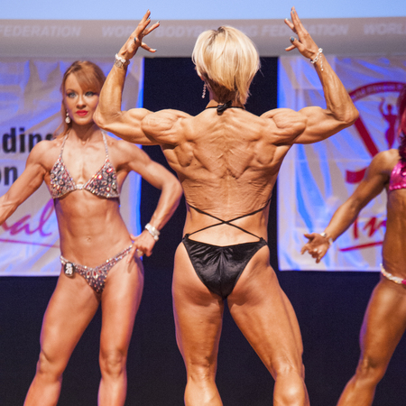 physique: MAASTRICHT, THE NETHERLANDS - OCTOBER 25, 2015: Female fitness model Gerbel Mikk flexes her muscles and shows her best physique in a back double biceps pose on stage at the World Grandprix Bodybuilding and Fitness of the WBBF-WFF on October 25, 2015 at th