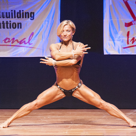 physique: MAASTRICHT, THE NETHERLANDS - OCTOBER 25, 2015: Female fitness model Gerbel Mikk flexes her muscles and shows her best physique in a front pose on stage at the World Grandprix Bodybuilding and Fitness of the WBBF-WFF on October 25, 2015 at the MECC Theatr Editorial