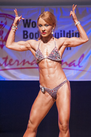 physique: MAASTRICHT, THE NETHERLANDS - OCTOBER 25, 2015: Female fitness model flexes her muscles and shows her best physique in a front double biceps  pose on stage at the World Grandprix Bodybuilding and Fitness of the WBBF-WFF on October 25, 2015 at the MECC The