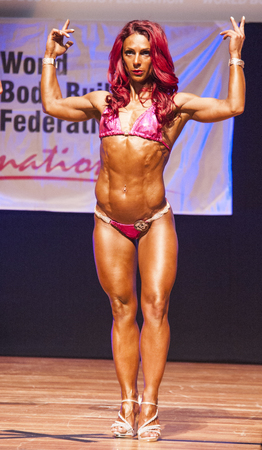 MAASTRICHT, THE NETHERLANDS - OCTOBER 25, 2015: Female fitness model flexes her muscles and shows her best physique in a front double biceps pose on stage at the World Grandprix Bodybuilding and Fitness of the WBBF-WFF on October 25, 2015 at the MECC Thea