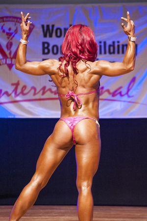 physique: MAASTRICHT, THE NETHERLANDS - OCTOBER 25, 2015: Female fitness model flexes her muscles and shows her best physique in a back double biceps pose on stage at the World Grandprix Bodybuilding and Fitness of the WBBF-WFF on October 25, 2015 at the MECC Theat