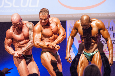 flex: MAASTRICHT, THE NETHERLANDS - OCTOBER 25, 2015: Male bodybuilders flex their muscles and show their best physique on stage at the World Grandprix Bodybuilding and Fitness of the WBBF-WFF on October 25, 2015 at the MECC Theatre in Maastricht, the Netherlan