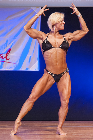physique: MAASTRICHT, THE NETHERLANDS - OCTOBER 25, 2015: Female fitness model Gerbel Mikk flexes her muscles and shows her best physique in a front double biceps pose on stage at the World Grandprix Bodybuilding and Fitness of the WBBF-WFF on October 25, 2015 at t Editorial