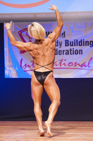 physique: MAASTRICHT, THE NETHERLANDS - OCTOBER 25, 2015: Female fitness model Gerbel Mikk flexes her muscles and shows her best physique in a back pose on stage at the World Grandprix Bodybuilding and Fitness of the WBBF-WFF on October 25, 2015 at the MECC Theatre