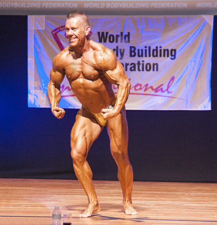 physique: MAASTRICHT, THE NETHERLANDS - OCTOBER 25, 2015: Male bodybuilder flexes his muscles and shows his best physique in a most muscular pose on stage at the World Grandprix Bodybuilding and Fitness of the WBBF-WFF on October 25, 2015 at the MECC Theatre in Maa Editorial