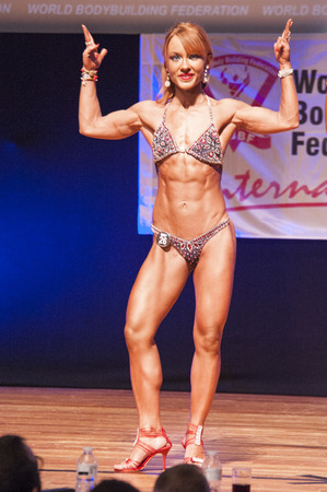 physique: MAASTRICHT, THE NETHERLANDS - OCTOBER 25, 2015: Female fitness model flexes her muscles and shows her best physique in a front double biceps pose on stage at the World Grandprix Bodybuilding and Fitness of the WBBF-WFF on October 25, 2015 at the MECC Thea