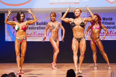 flex: MAASTRICHT, THE NETHERLANDS - OCTOBER 25, 2015: Female bodybuilders Gerbel Mikk and Sonja den Breems-Tanamal flex their muscles and show their best physique in a front double biceps pose on stage at the World Grandprix Bodybuilding and Fitness of the WBBF Editorial
